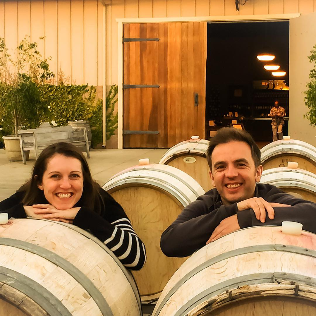 couple by wine barrels